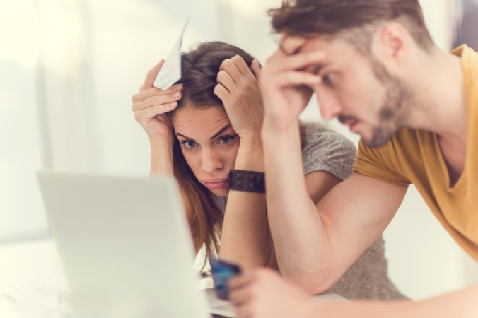 Couple in emotional distress staring at laptop screen